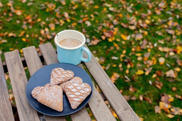 Xícara de café com biscoitos em forma de coração em uma mesa na temporada de outono