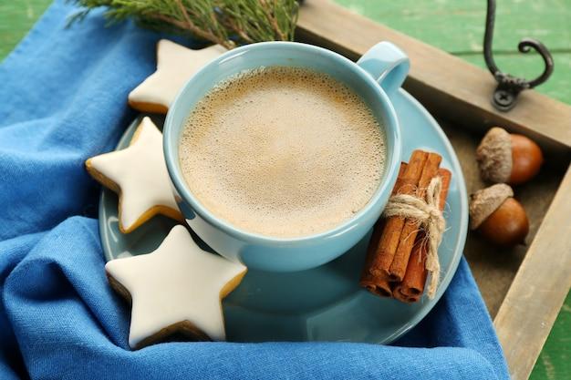 Xícara de café com biscoitos em forma de estrela no guardanapo na bandeja de madeira