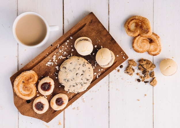 Xícara de café com biscoitos na placa de madeira