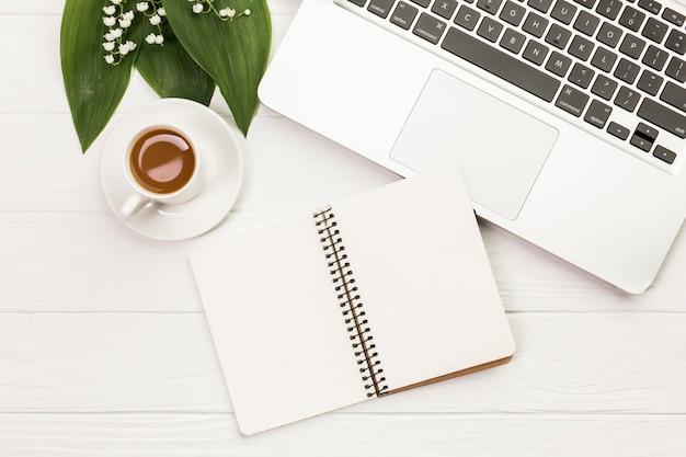 Xícara de café com bloco de notas em espiral perto do laptop na mesa de madeira branca