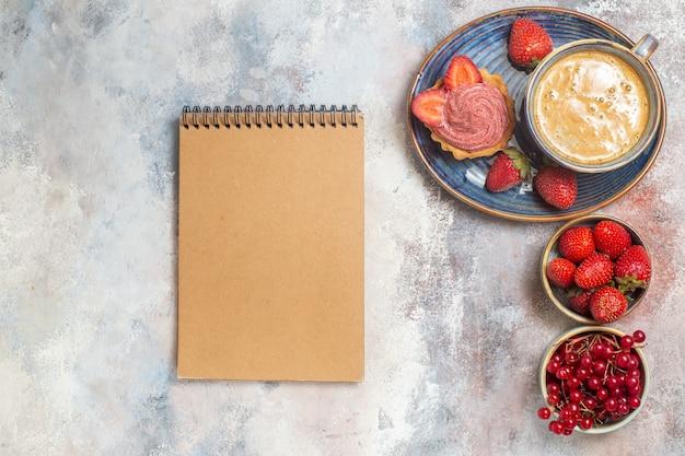 Xícara de café com bolo e frutas vermelhas em um bolo de biscoito doce de chão claro com vista de cima
