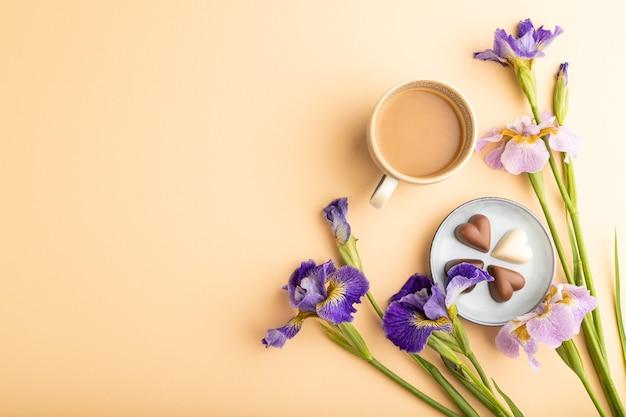 Xícara de café com bombons de chocolate e flores de íris lilás em fundo laranja pastel. vista do topo