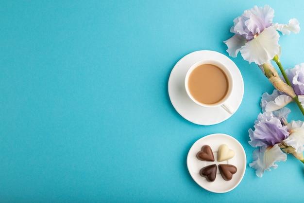 Xícara de café com bombons de chocolate e flores de íris lilás sobre fundo azul pastel. vista do topo,
