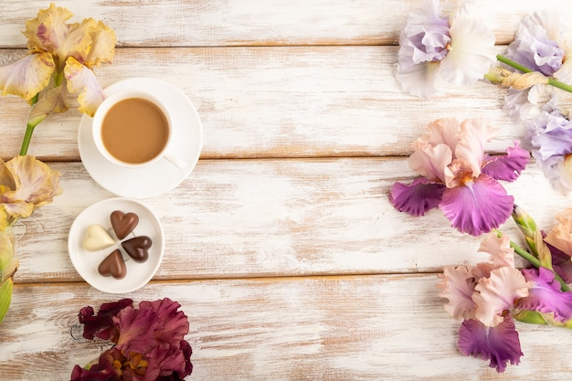 Xícara de café com bombons de chocolate, flores lilás e roxas de íris em fundo branco de madeira.