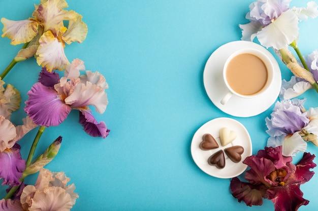 Xícara de café com bombons de chocolate, flores lilás e roxas de íris sobre fundo azul pastel.