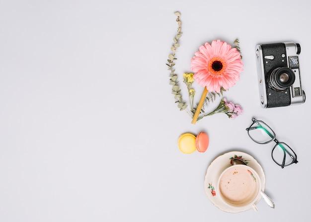 Xícara de café com botão de flor, câmera e óculos