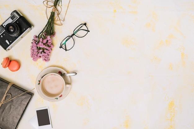 Xícara de café com buquê de flores, câmera e óculos na mesa