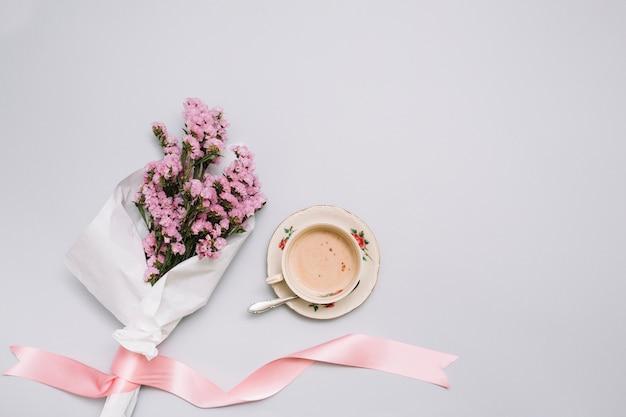 Xícara de café com buquê de flores na mesa