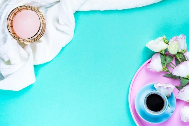 Xícara de café com buquê rosa eustoma em uma bandeja de rosas, manta e vela sobre fundo azul, configuração plana.