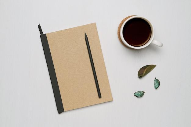 Xícara de café com caderno e lápis preto sobre fundo branco de madeira