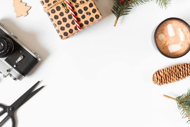 Xícara de café com caixa de presente e câmera na mesa