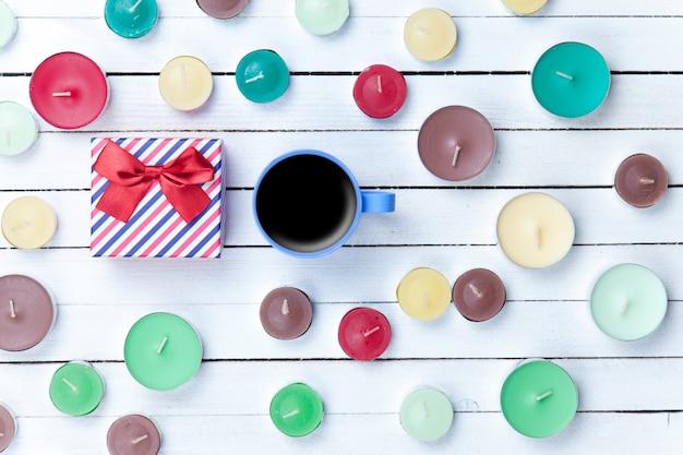 Xícara de café com caixa de presente e velas