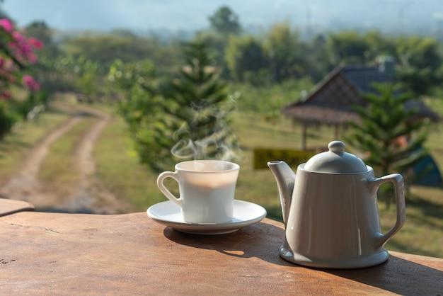 Xícara de café com caneca de café branco na mesa de madeira com cenário de montanha e campo de plantas em segundo plano