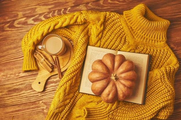 Xícara de café com canela e abóbora na mesa de madeira com livro e blusa
