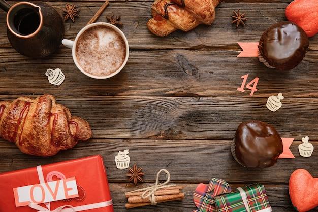 Xícara de café com canela na mesa de madeira escura com doce de padaria