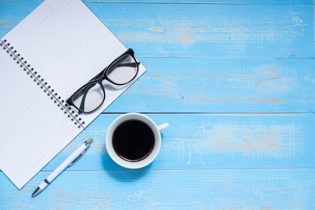 Xícara de café com caneta, caderno e óculos de olhos