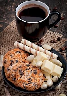 Xícara de café com chocolate branco, amêndoas e biscoitos