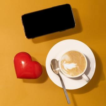 Xícara de café com chocolate, coração vermelho, telefone em uma mesa