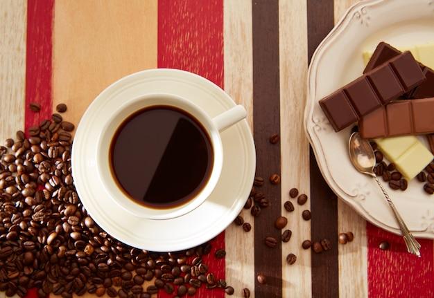 Xícara de café com chocolate e grãos de café