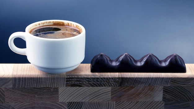 Xícara de café com chocolate em uma moldura de madeira branca. comida de sobremesa