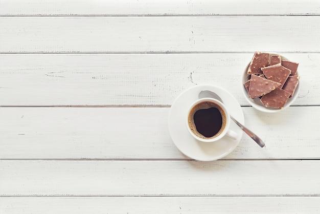 Xícara de café com chocolate na mesa de madeira.
