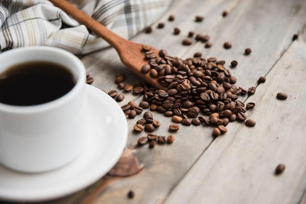 Xícara de café com colher cheia de grãos