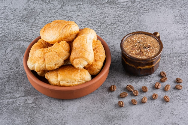 Xícara de café com croissant caseiro em uma tigela sobre o cinza.