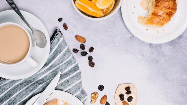 Xícara de café com croissant na placa