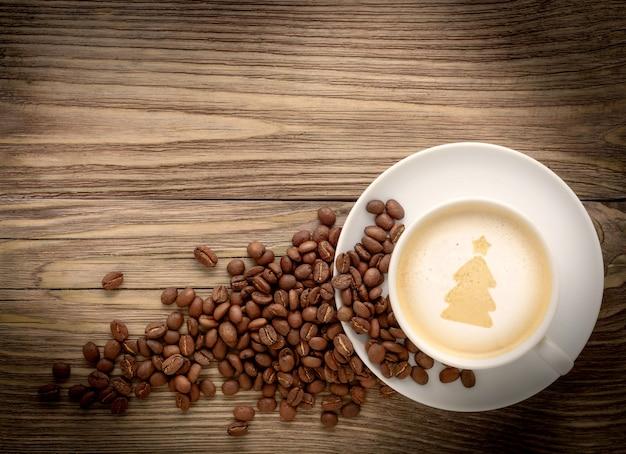 Xícara de café com desenho de árvore de natal na mesa de madeira