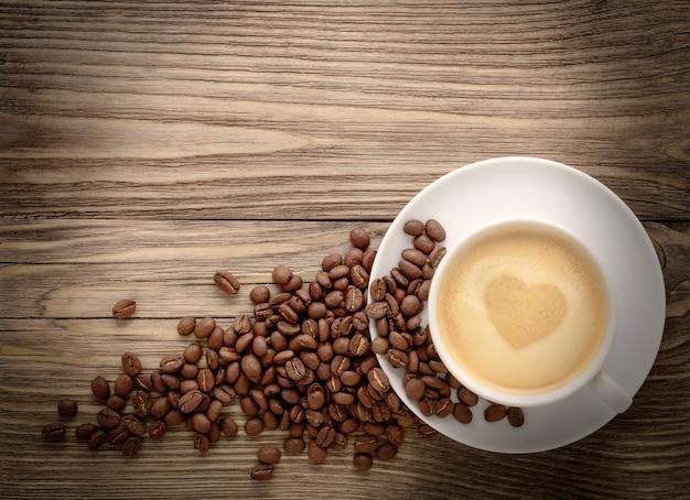 Xícara de café com desenho de coração e grãos de café