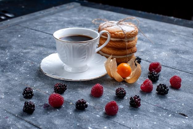Xícara de café com diferentes frutas e biscoitos sanduíche na mesa cinza.