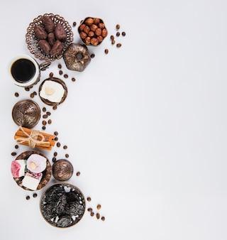 Xícara de café com doces orientais e avelãs