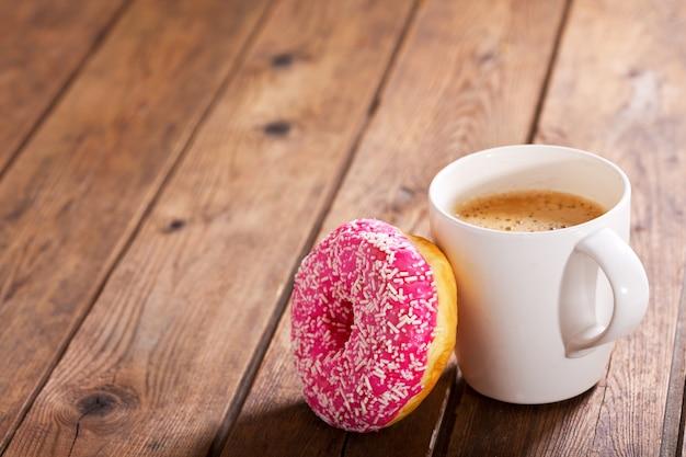 Xícara de café com donut na mesa de madeira
