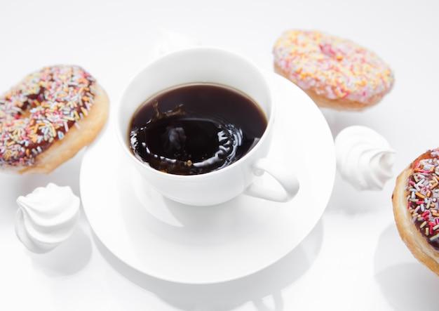 Xícara de café com donuts e merengues em movimento