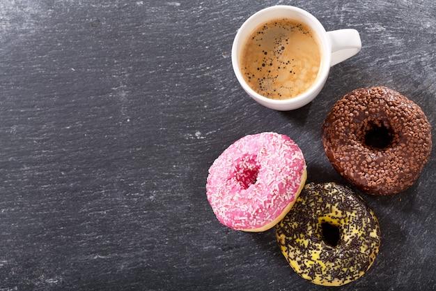 Xícara de café com donuts na mesa escura, vista de cima