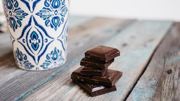 Xícara de café com enfeite azul e chocolate em uma mesa de madeira