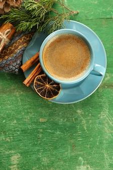 Xícara de café com especiarias doces no guardanapo na mesa de madeira verde
