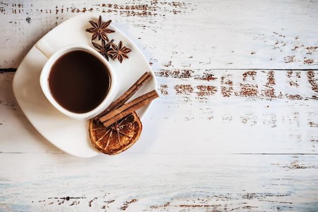 Xícara de café com especiarias na textura da mesa de madeira