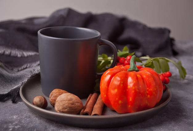 Xícara de café com especiarias, pequena abóbora e rowan