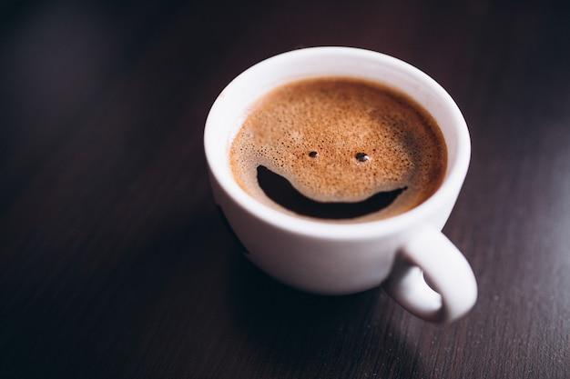 Xícara de café com espuma, cara de sorriso, na mesa isolada