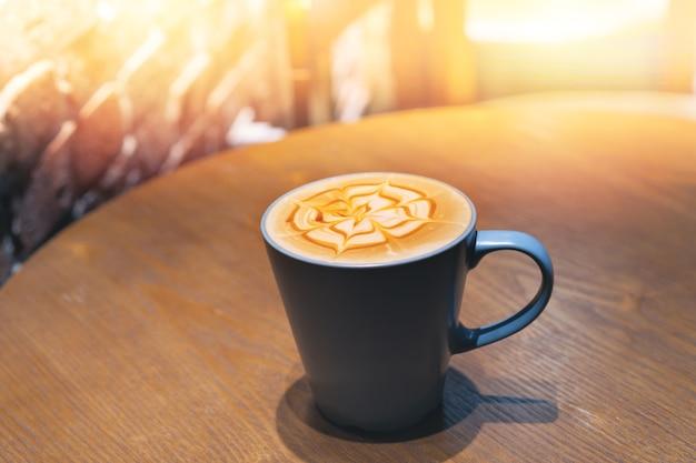 Xícara de café com espuma em forma de flor na mesa de madeira