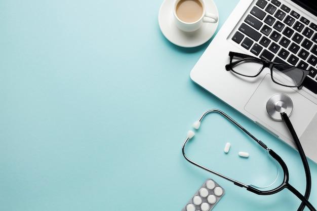 Xícara de café com estetoscópio na prancheta e pílulas sobre a mesa