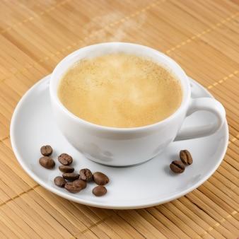 Xícara de café com feijão em fundo fosco de bambu