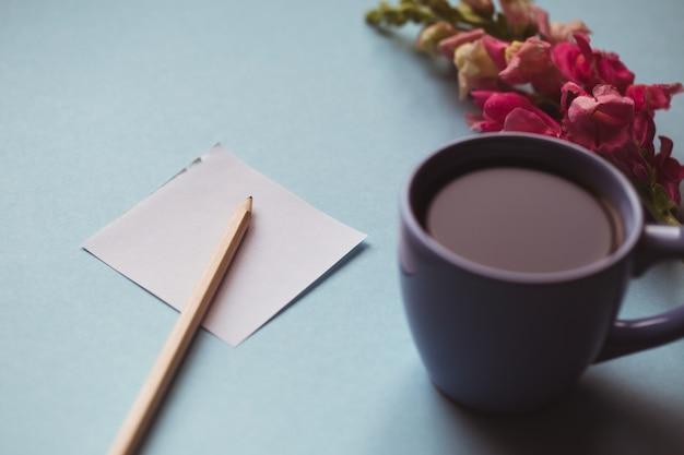 Xícara de café com flor de primavera e notas de bom dia na mesa azul