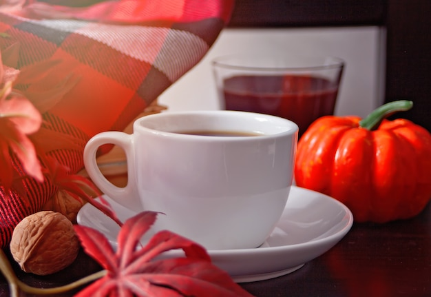 Xícara de café com folhas de outono e abóbora