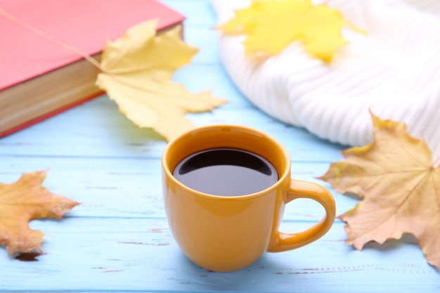 Xícara de café com folhas de outono e livro velho em fundo de madeira