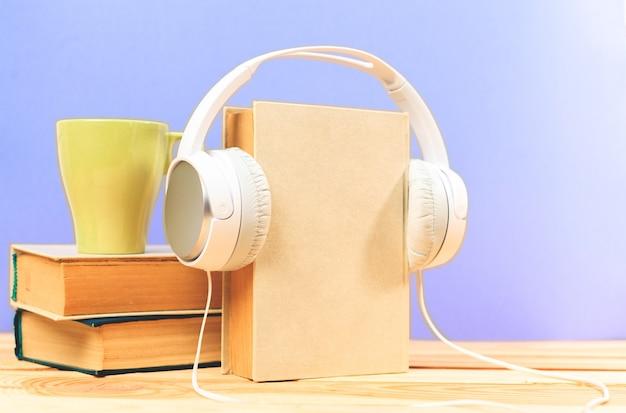 Xícara de café com fones de ouvido na madeira