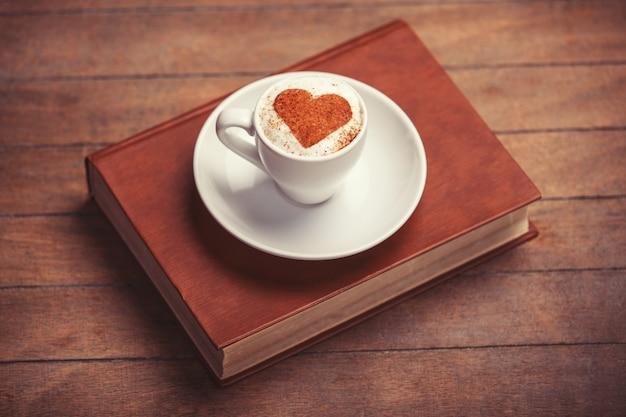 Xícara de café com forma de coração e livro sobre uma mesa de madeira