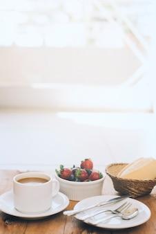 Xícara de café com frutas frescas e talheres na placa contra o fundo de madeira