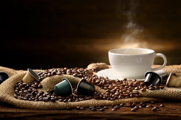 Xícara de café com fumaça e grãos de café e cápsulas de café em saco de aniagem na velha mesa de madeira